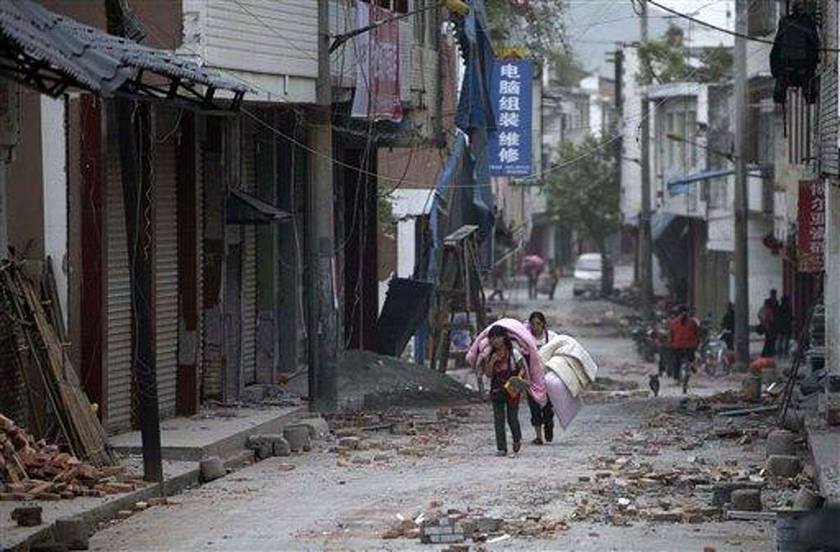 In this photo released by China's Xinhua news agency, people carrying their belongings walk in quake-damaged Gucheng Village, Longmen Township, Lushan County, southwest China's Sichuan Province, Saturday, April 20, 2013. A powerful earthquake struck the steep hills of Sichuan province Saturday, nearly five years after a devastating quake wreaked widespread damage across the region. (AP Photo/Xinhua, Fei Maohua) NO SALES