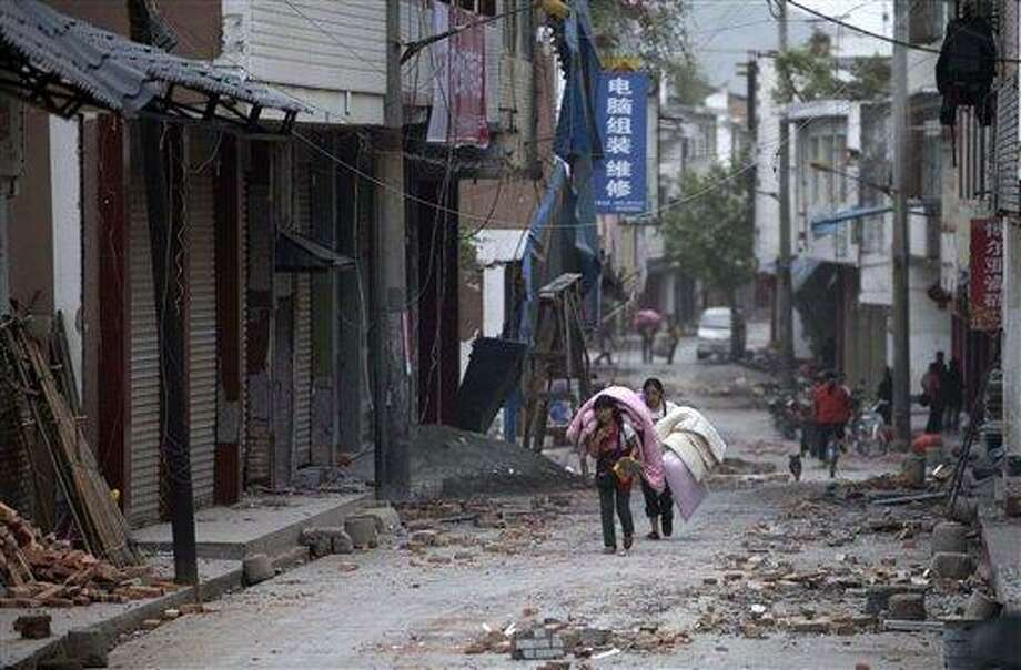 In this photo released by China's Xinhua news agency, people carrying their belongings walk in quake-damaged Gucheng Village, Longmen Township, Lushan County, southwest China's Sichuan Province, Saturday, April 20, 2013. A powerful earthquake struck the steep hills of Sichuan province Saturday, nearly five years after a devastating quake wreaked widespread damage across the region. (AP Photo/Xinhua, Fei Maohua) NO SALES Photo: AP / Xinhua