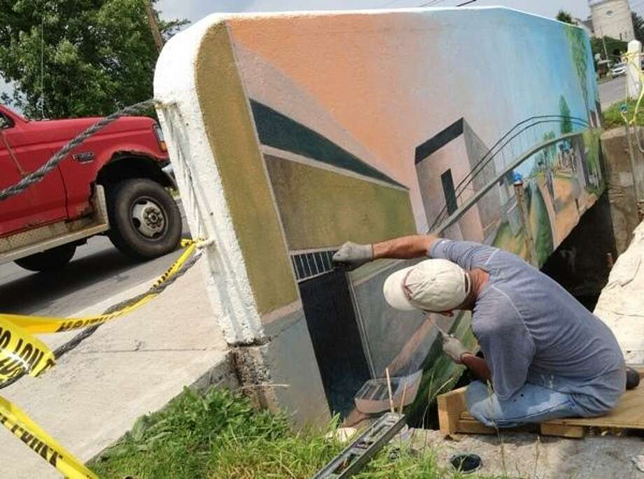 JOHN HAEGER @ONEIDAPHOTO ON TWITTER/ONEIDA DAILY DISPATCH Artist Corky Goss works on a section of the mural depicting the Eric Canal on the bridge on Main Street in the village of Canastota on Monday, June 24, 2013.
