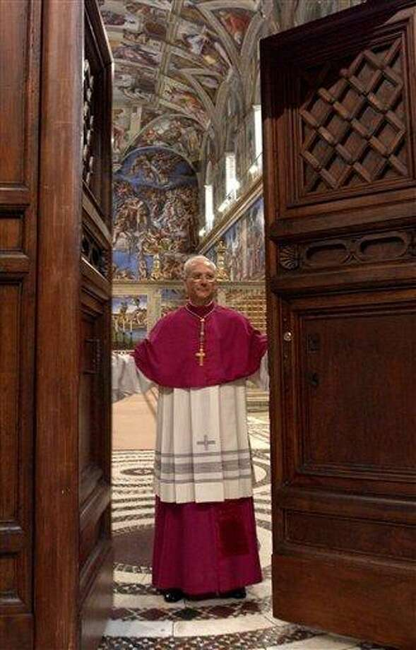 "FILE -- In this photo from files taken on April 18, 2005 and released by the Vatican paper L'Osservatore Romano, Master of Liturgical Celebrations Archbishop Piero Marini closes the door of the Sistine Chapel at the Vatican, after proclaiming the ""extra omnes"", which is the Latin order for all those not taking part in the conclave to leave the chapel, at the beginning of the conclave. Next month's conclave to elect the 266th leader of the world's 1.2 billion Catholics will have all the trappings of papal elections past, with the added twist that the this time around the current pope is still very much alive. The conclave begins with the cardinals in their red cassocks processing into the Sistine Chapel, chanting the hypnotic Litany of Saints or Veni Creator imploring the intervention of the Holy Spirit as they take their places before Michelangelo's ""Last Judgment."" (in background) (AP Photo/Osservatore Romano, ho) Photo: AP / Osservatore Romano"