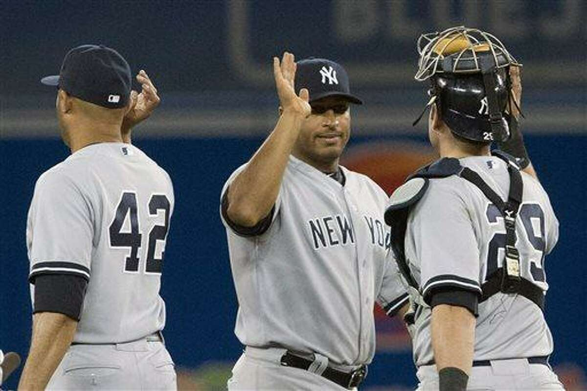 New York Yankees' Vernon Wells, center, celebrates with teammates Mariano Rivera, left, and Francisco Cerveili after defeating the Toronto Blue Jays 5-3 in a baseball game in Toronto, Saturday, April 20, 2013. (AP Photo/The Canadian Press, Chris Young)