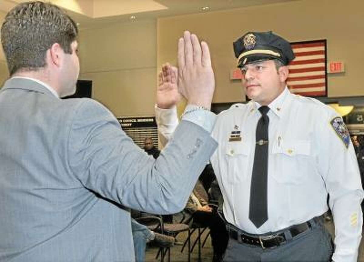 Catherine Avalone/The Middletown Press Mayor Dan Drew swears in Michael Timbro as the new Deputy Police Chief of Middletown Friday night at council chambers at city hall.