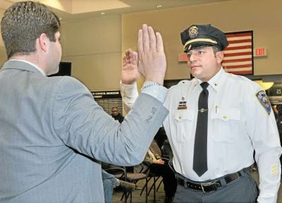 Catherine Avalone/The Middletown Press Mayor Dan Drew swears in Michael Timbro as the new Deputy Police Chief of Middletown Friday night at council chambers at city hall. / TheMiddletownPress