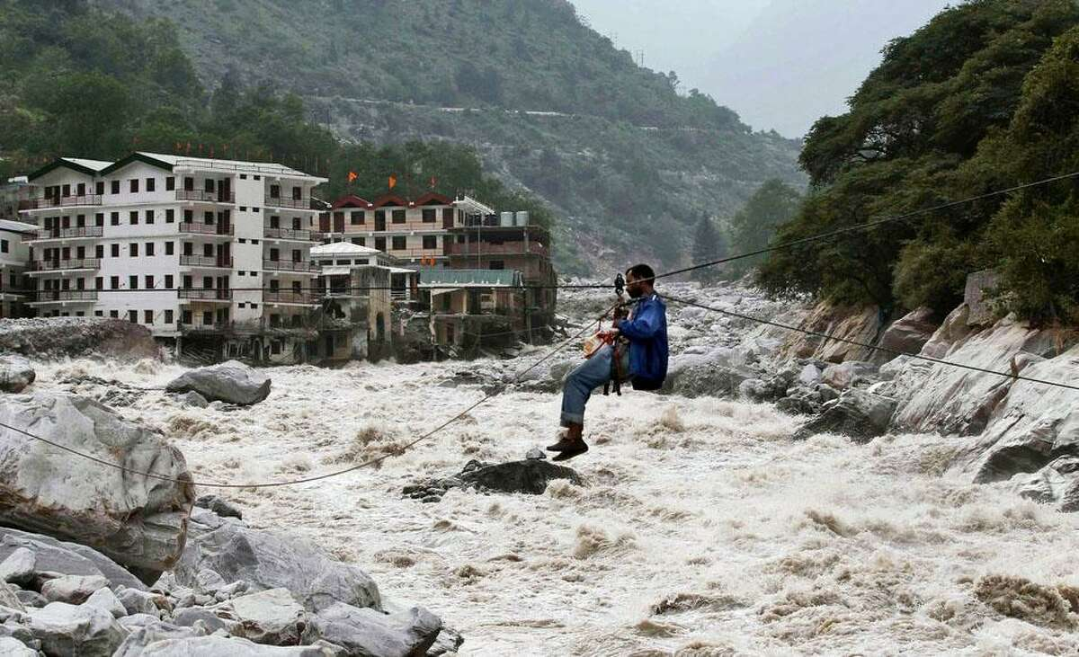 An Indian man crosses over a swollen river with the help of a rope in Govindghat, India, Sunday, June 23, 2013. Bad weather hampered efforts Sunday to evacuate thousands of people stranded in the northern India state of Uttarakhand, where at least 1,000 people have died in monsoon flooding and landslides, army officials said. (AP Photo/Rafiq Maqbool)