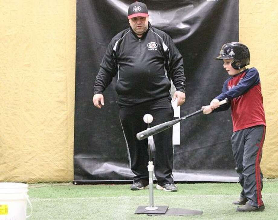 """Dispatch Staff Photo by JOHN HAEGER <a href=""""http://twitter.com/oneidaphoto"""">twitter.com/oneidaphoto</a> Dave Muraco works with Devin Smith during a hitting lesson in Canastota on Thursday, Feb. 14, 2013 Photo: Oneida Daily Dispatch / Oneida Daily Dispatch"""