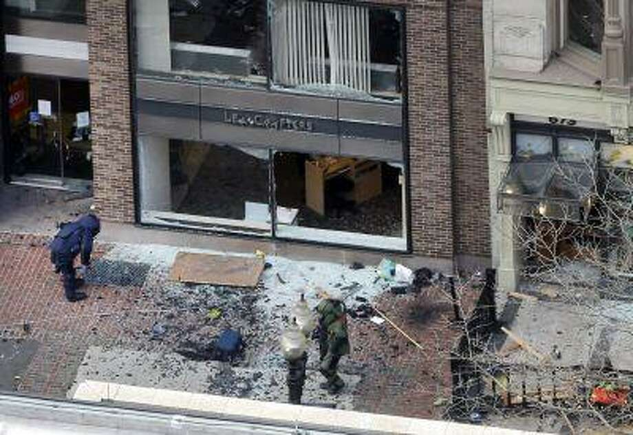 One of the blast sites on Boylston Street near the finish line of the 2013 Boston Marathon is investigated by two people in protective suits in the wake of two blasts in Boston Monday, April 15, 2013. (AP Photo/Elise Amendola) Photo: AP / AP