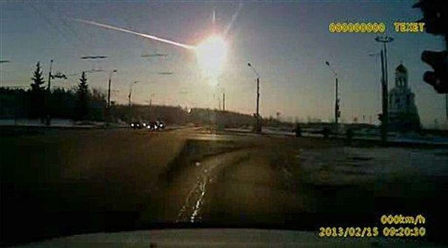 In this frame grab made from dashboard camera video, a meteor streaks through the sky over Chelyabinsk, about 1500 kilometers (930 miles) east of Moscow, Friday, Feb. 15, 2013. With a blinding flash and a booming shock wave, the meteor blazed across the western Siberian sky Friday and exploded with the force of 20 atomic bombs, injuring more than 1,000 people as it blasted out windows and spread panic in a city of 1 million. (AP Photo/AP Video) Photo: AP / AP Video
