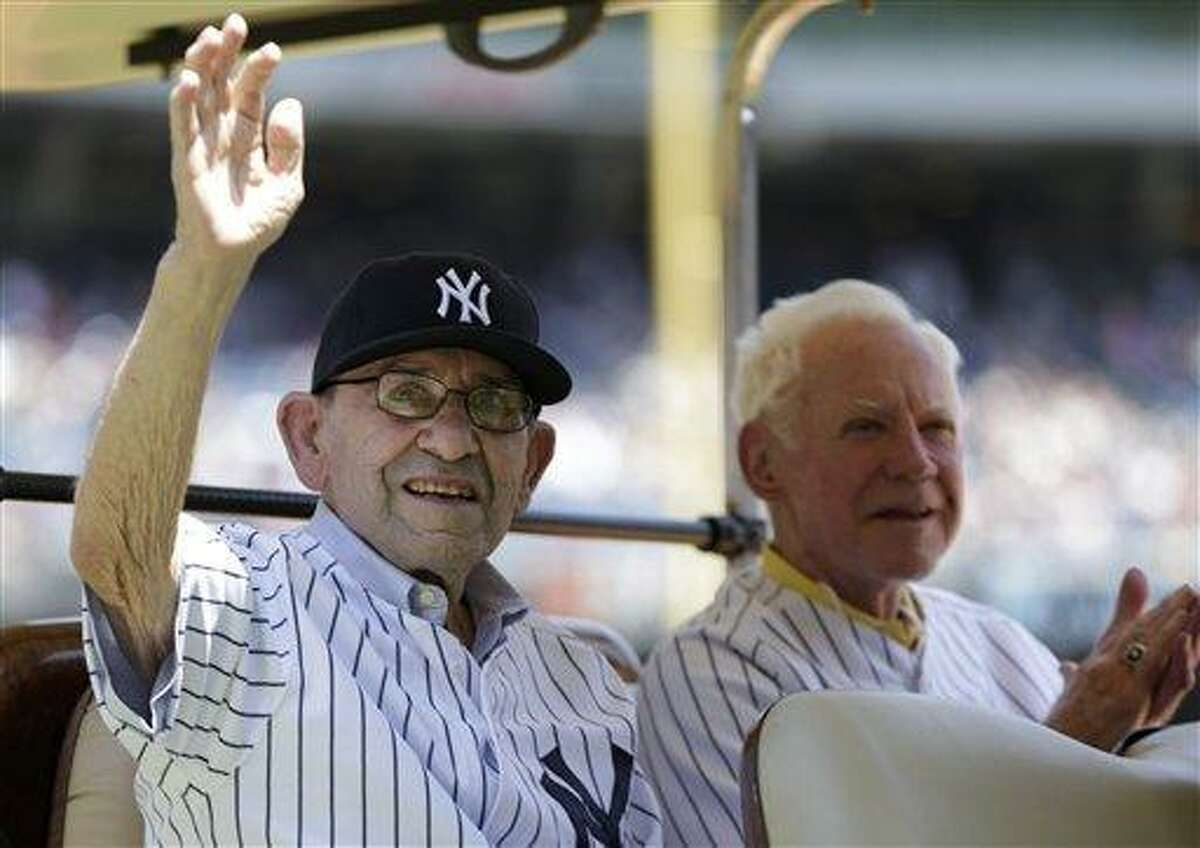 New York Yankees Hall-of-Famer Yogi Berra, left, waves as fellow Hall-of-Famer Whitey Ford applauds during introductions before the Yankees Old Timers Day baseball game on Sunday, June 23, 2013, at Yankee Stadium in New York. (AP Photo/Kathy Willens)
