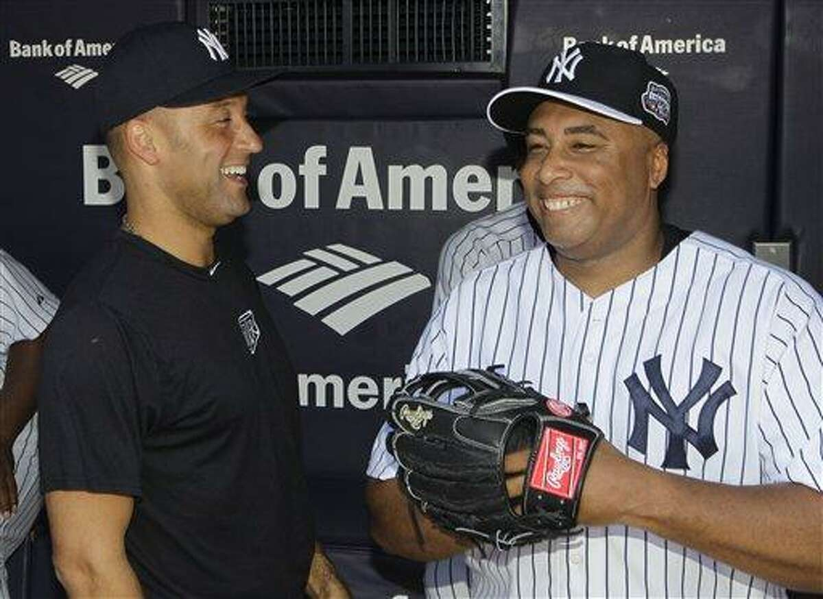 New York Yankees shortstop Derek Jeter, left, who is on the disabled list, shares a laugh with former New York Yankees outfielder Bernie Williams in the dugout before the Old Timers Day baseball game Sunday, June 23, 2013, in New York. (AP Photo/Kathy Willens)