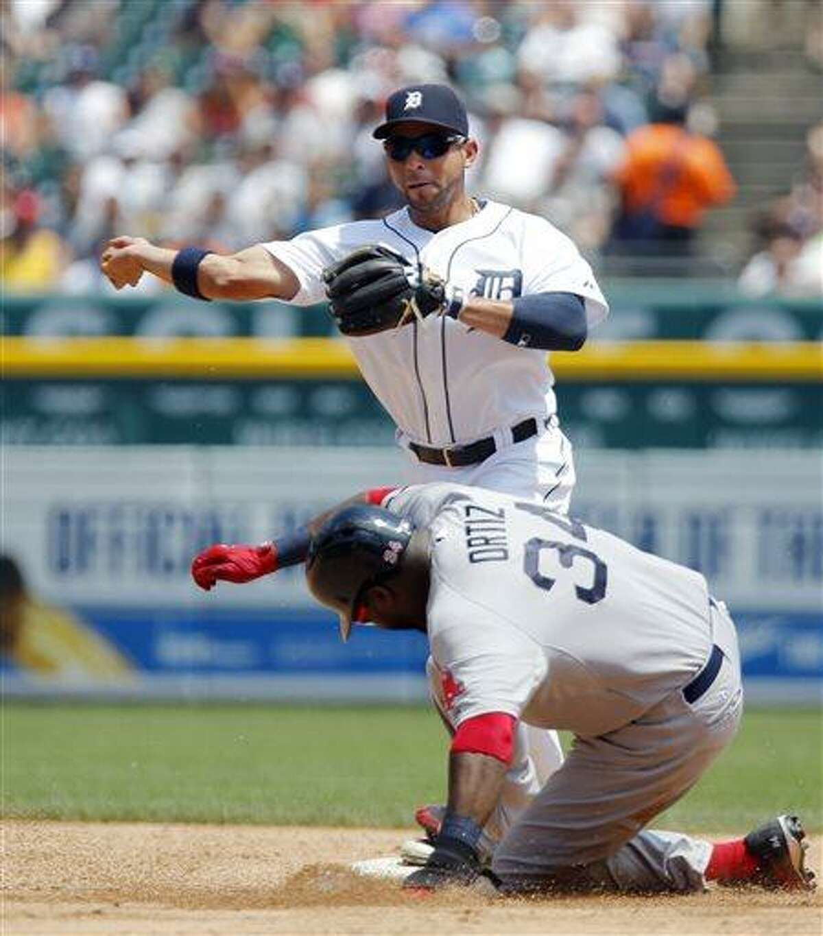 Detroit Tigers second baseman Omar Infante, top, turns the ball after getting a force-out on Boston Red Sox's David Ortiz (34) in the third inning of a baseball game on Sunday, June 23, 2013, in Detroit. Infante's throw was wild to first base and Red Sox's Mike Napoli was safe on the play. (AP Photo/Duane Burleson)