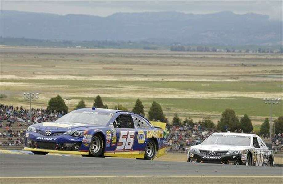Martin Truex Jr. (56) and Brian Vickers (55) compete in the NASCAR Sprint Cup series auto race on Sunday, June 23, 2013, in Sonoma, Calif. (AP Photo/Eric Risberg) Photo: AP / AP
