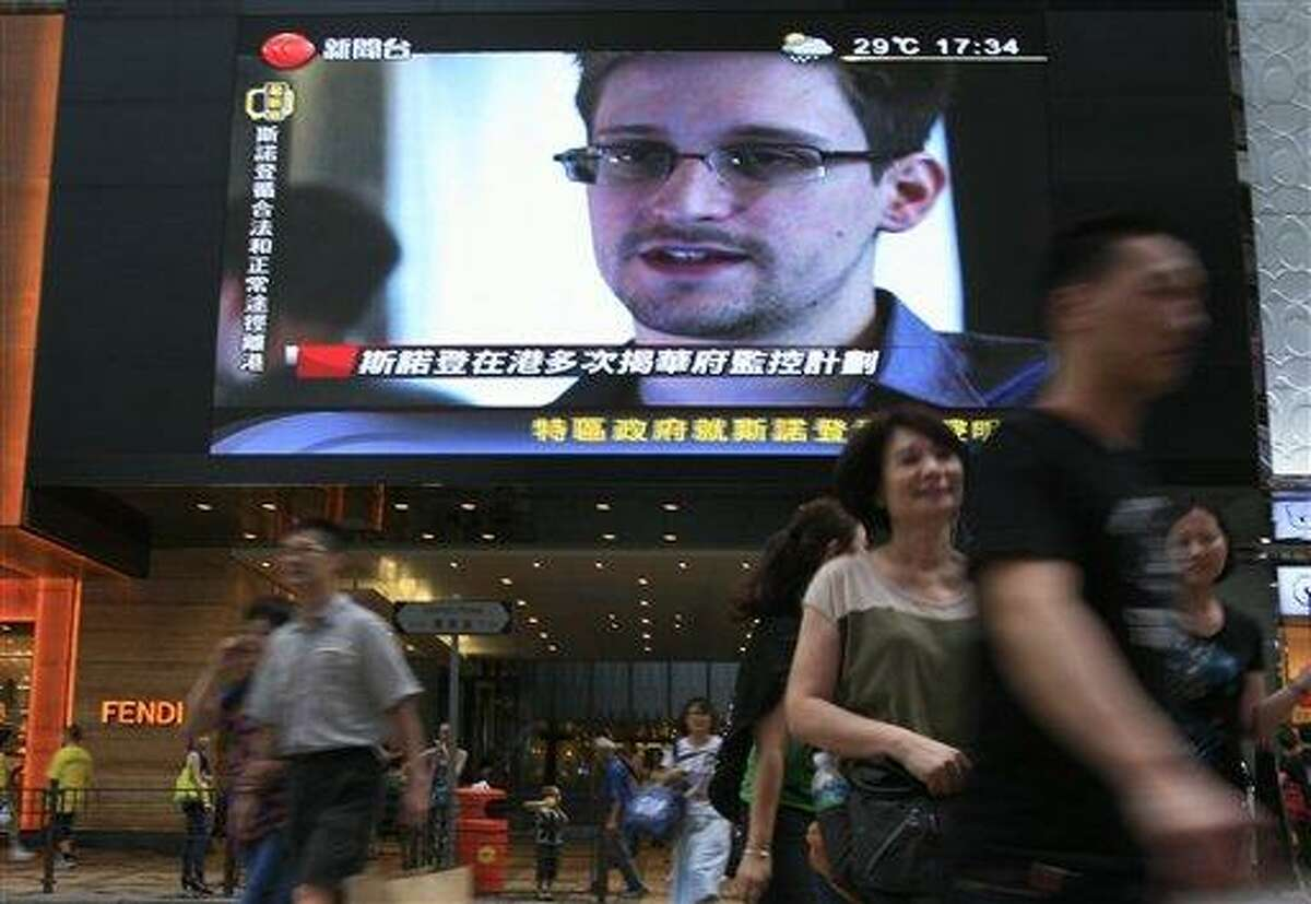 A TV screen shows a news report of Edward Snowden, a former CIA employee who leaked top-secret documents about sweeping U.S. surveillance programs, at a shopping mall in Hong Kong Sunday, June 23, 2013. The former National Security Agency contractor wanted by the United States for revealing two highly classified surveillance programs has been allowed to leave for a