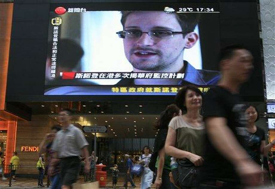 "A TV screen shows a news report of Edward Snowden, a former CIA employee who leaked top-secret documents about sweeping U.S. surveillance programs, at a shopping mall in Hong Kong Sunday, June 23, 2013. The former National Security Agency contractor wanted by the United States for revealing two highly classified surveillance programs has been allowed to leave for a ""third country"" because a U.S. extradition request did not fully comply with Hong Kong law, the territory's government said Sunday. (AP Photo/Vincent Yu) Photo: AP / AP"