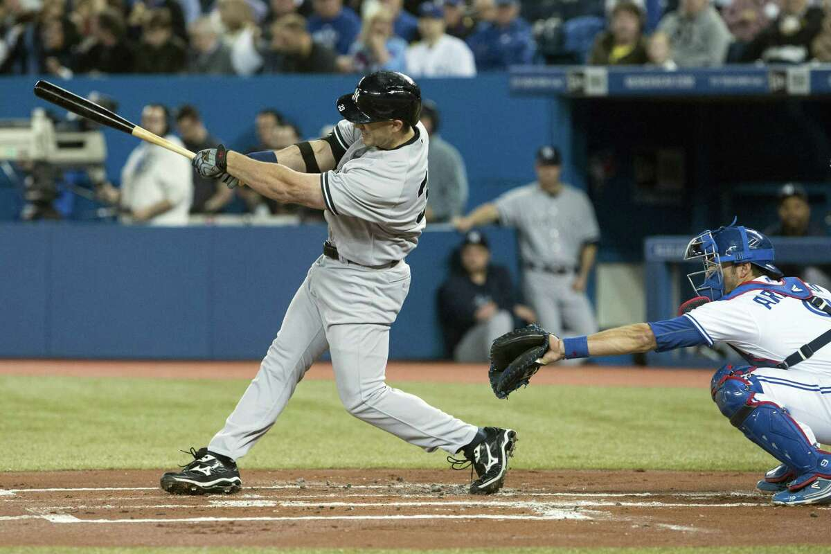 New York Yankees' Travis Hafner hits an RBI double off Toronto Blue Jays pitcher Brandon Morrow during the first inning of a baseball game in Toronto on Friday, April 19, 2013. (AP Photo/The Canadian Press, Chris Young)