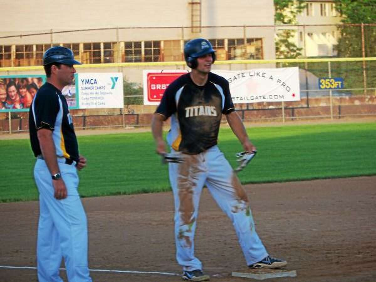 Wamogo graduate Mike Odenwaelder talks with Titan coach Misha Dworken at third base after Odenwaelder blasted a triple Sunday night.Peter Wallace-Register Citizen