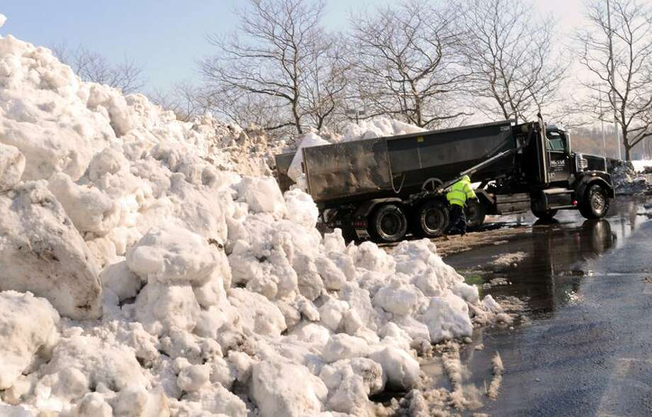 The dumping of collected Blizzard of 2013 snow  Friday afternoon, February 15, 2013 from private contractor  tri-axle dump trucks into 4 created aisles in the parking lot of East Shore Park on Woodward Avenue and Tuttle Street in New Haven, Conn. The aisles, where the snow is deposited, run 150-yards deep and approximately 25-feet high. 2-years ago total blizzard snowfall deposited there ran at approximately 150 truckloads. Just for the Blizzard of 2013 to date on 2:00 p.m February 15, 2013, over 800 truckloads were deposited. Photo by Peter Hvizdak / New Haven Register Photo: New Haven Register / ©Peter Hvizdak /  New Haven Register