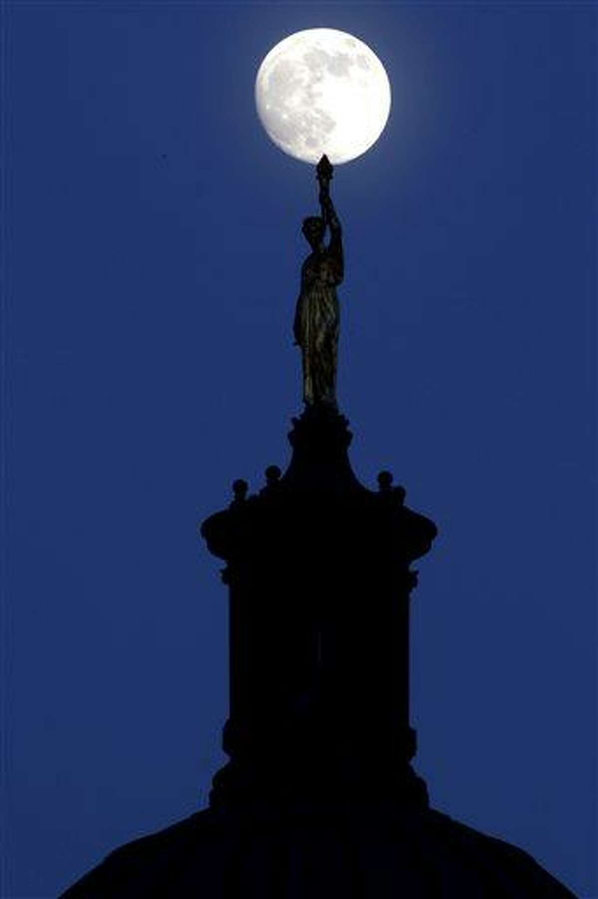 """The moon in its waxing gibbous stage shines over a statue entitled """"Enlightenment Giving Power"""" by John Gelert, which sits at the top of the dome of the Bergen County Courthouse in Hackensack, N.J., Friday, June 21, 2013. The moon, which will reach its full stage on Sunday, is expected to be 13.5 percent closer to earth during a phenomenon known as supermoon. (AP Photo/Julio Cortez)"""