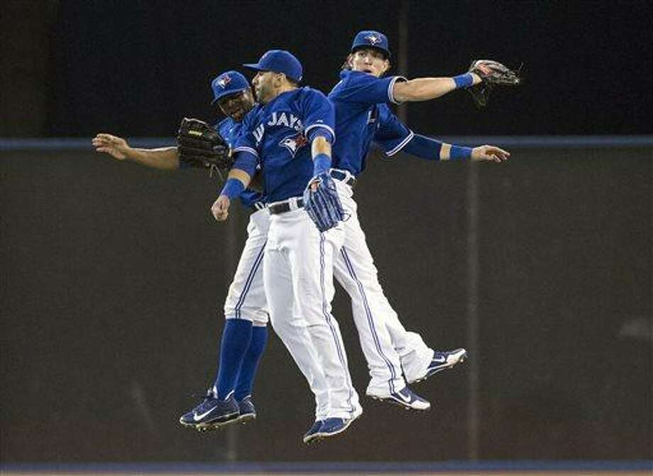 Toronto Blue Jays' Rajai Davis, left,  Jose Bautista, center,  and Colby Rasmus celebrate their 4-2 win over the Baltimore Orioles after a  baseball game in Toronto, Saturday June 22, 2013. (AP Photo/the Canadian Press, Chris Young) Photo: AP / CP