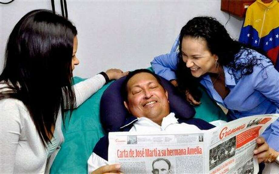 In this photo released Friday, Feb. 15, 2013 by Miraflores Presidential Press Office, Venezuela's President Hugo Chavez, center, poses for a photo with his daughters, Maria Gabriela, left, and Rosa Virginia as he holds a copy of Cuba's state newspaper Granma at an unknown location in Havana, Cuba, Thursday, Feb. 14, 2013. Chavez remains in Havana undergoing unspecified treatments following his fourth cancer-related operation on Dec. 11. He has hasn't been seen or spoken publicly in more than two months. (AP Photo/Miraflores Presidential Press Office) Photo: AP / MIRAFLORES PRESS OFFICE