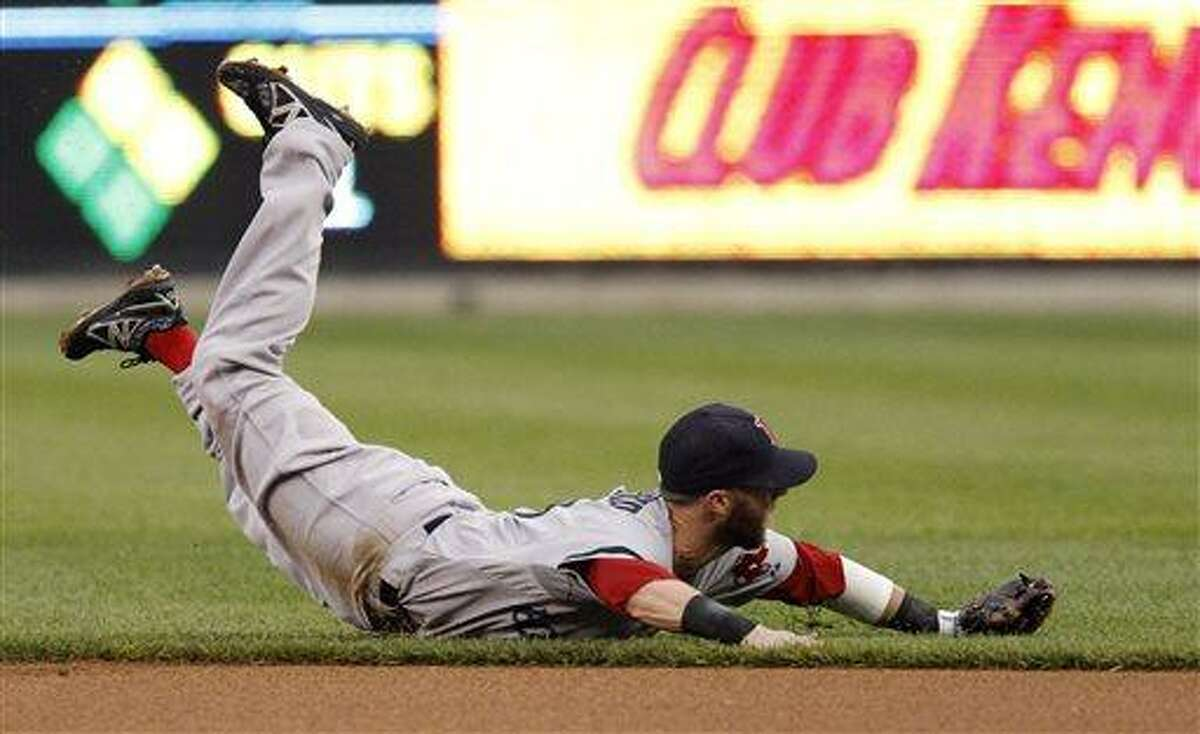 Boston Red Sox second baseman Dustin Pedroia lands on the field after making a diving attempt on a single by Detroit Tigers' Andy Dirks in the first inning of a baseball game, Saturday, June 22, 2013, in Detroit. (AP Photo/Duane Burleson)
