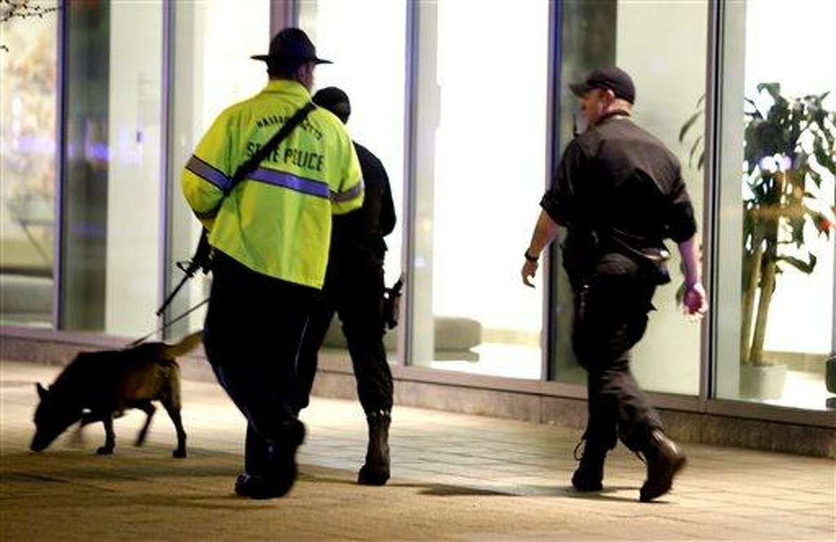 Officials patrol an area at Massachusetts Institute of Technology following reports of a shooting, Thursday, April 18, 2013, in Boston. State police say a campus police officer at the school has died from injuries in a shooting on the campus outside Boston. State police spokesman Dave Procopio says the shooting took place about 10:30 p.m. outside an MIT building. The officer was described as a male but no further information about him was released. The city continues to cope following Monday's explosions near the finish line of the Boston Marathon. (AP Photo/Julio Cortez)