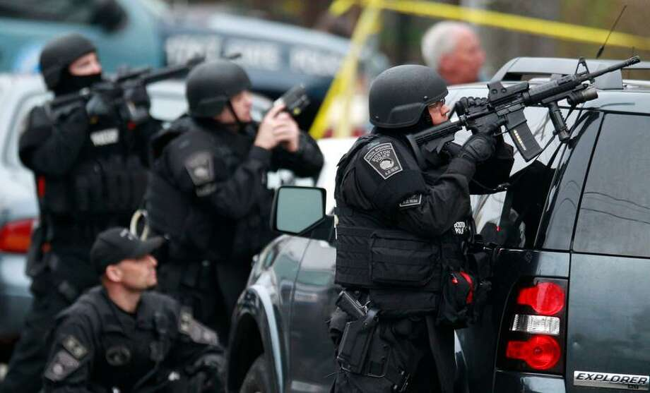 Police in tactical gear surround an apartment building while looking for a suspect in the Boston Marathon bombings in Watertown, Mass., Friday, April 19, 2013. All residents of Boston were ordered to stay in their homes Friday morning as the search for the surviving suspect in the marathon bombings continued after a long night of violence that left another suspect dead. (AP Photo/Charles Krupa) Photo: ASSOCIATED PRESS / THE ASSOCIATED PRESS2013