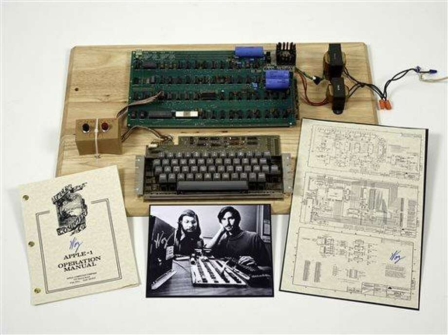 "This undated photo provided by Christie's Auction House shows an ""Apple 1"" prototype computer, built in 1976, accompanied by an operation manual and schematic as well as a photo of its inventors, Steve Wozniak, left, and Steve Jobs. One of the very first Apple 1 computers, it goes on sale later this month at Christie's auction house, the latest in a recent run of vintage tech sales that have attracted some eye-popping prices.   (AP Photo/Christies Images Ltd. 2013) Photo: AP / Christies Images LTD.2013"