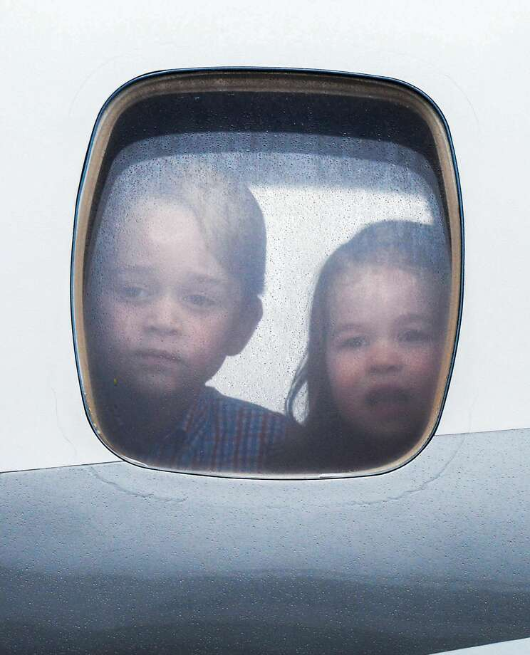 Princess Charlotte of Cambridge and Prince George of Cambridge look out of the window of the plane as they arrive at Warsaw airport during an official visit to Poland and Germany on July 17, 2017 in Warsaw, Poland. Photo: Pool/Samir Hussein/Samir Hussein/WireImage