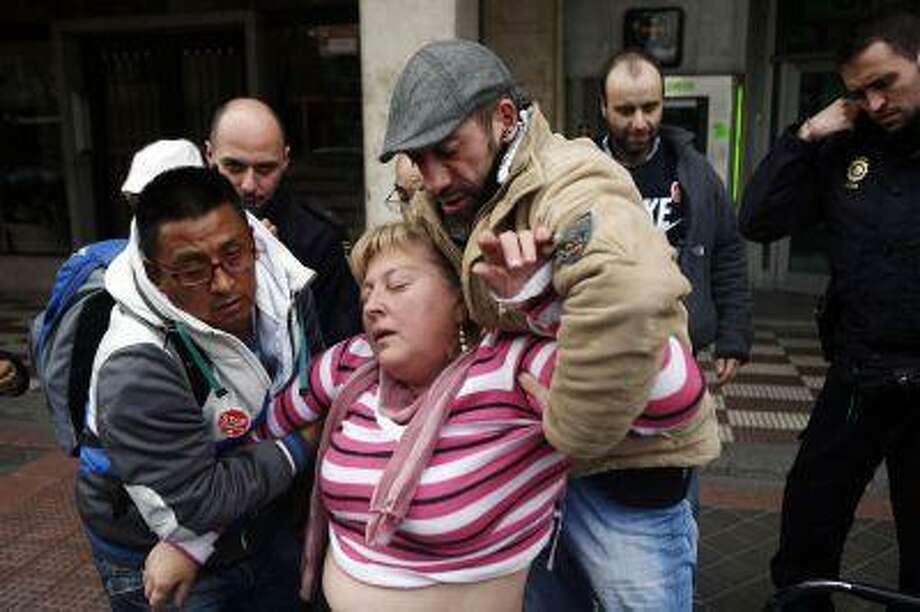 Hanna Hrytsyuk is helped by members of the Mortgage Victims' Platform (PAH) after having an anxiety attack as she was trying to convince her bank to stop an eviction from her home. Photo: REUTERS / X01622