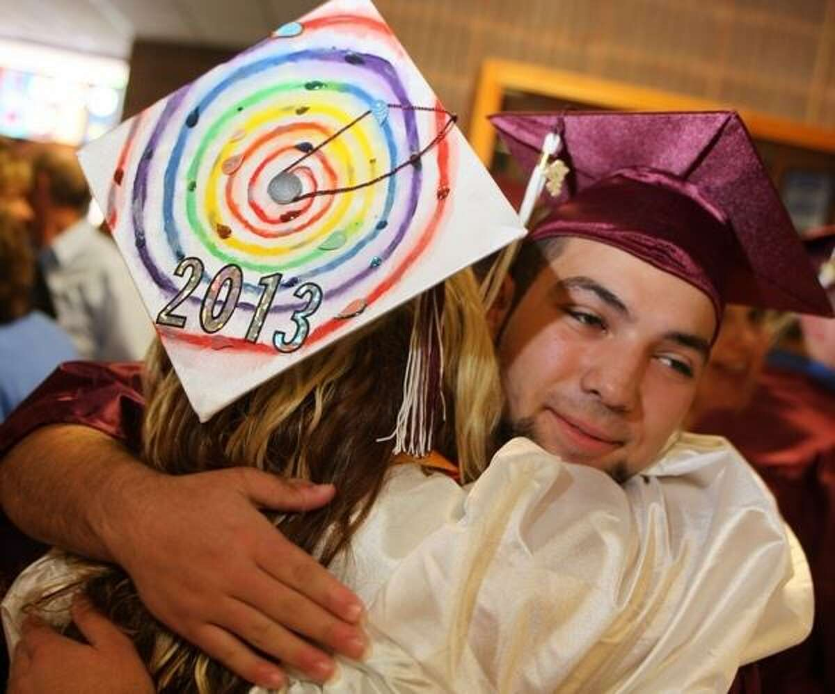 JOHN HAEGER @ONEIDAPHOTO ON TWITTER/ONEIDA DAILY DISPATCH Jacob Whitehall hugs classmate Samantha Streator before the start of the Canastota High School 132nd Commencement exercises on Saturday, June 22, 2013 in Canastota.