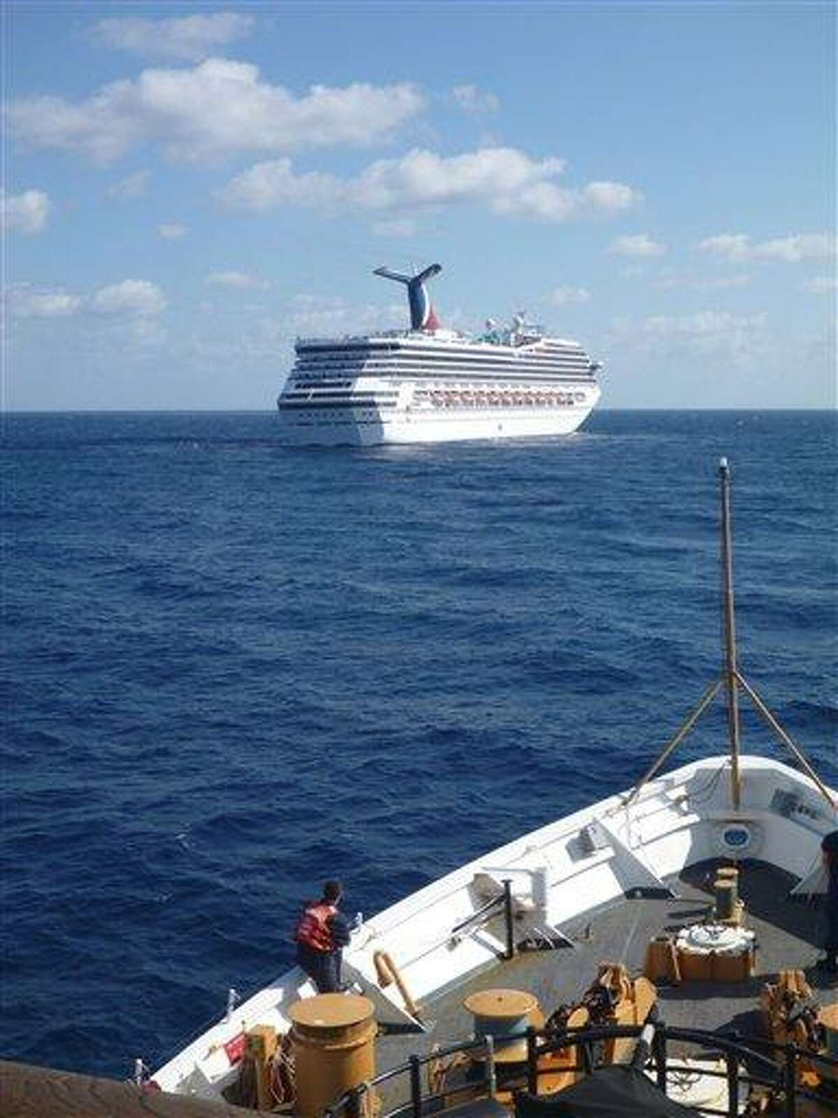 In this image released by the U.S. Coast Guard on Feb. 11, 2013, the Coast Guard Cutter Vigorous patrols near the cruise ship Carnival Triumph in the Gulf of Mexico, Feb. 11, 2013. The Carnival Triumph has been floating aimlessly about 150 miles off the Yucatan Peninsula since a fire erupted in the aft engine room early Sunday, knocking out the ship's propulsion system. No one was injured and the fire was extinguished. AP Photo/U.S. Coast Guard- Lt. Cmdr. Paul McConnell