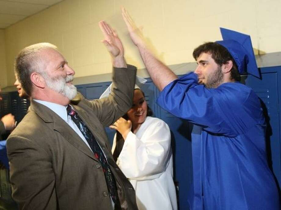 JOHN HAEGER @ONEIDAPHOTO ON TWITTER/ONEIDA DAILY DISPATCH Madison Central School science teacher Dan Saulsgiver high fives Billy Williams before the start of the commencement on Friday, June 21, 2013 in Madison.