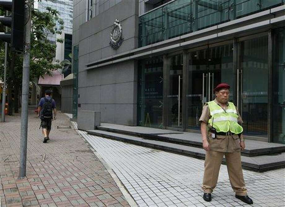 A security guard stands in front of the Police headquarters in Hong Kong Saturday, June 22, 2013. Former National Security Agency contractor Edward Snowden, believed to be holed up in Hong Kong, has admitted providing information to the news media about two highly classified NSA surveillance programs. It is not known if the U.S. government has made a formal extradition request to Hong Kong, and the Hong Kong government had no immediate reaction to the charges against Snowden. Police Commissioner Andy Tsang, when was asked about the development, told reporters only that the case would be dealt with according to the law. (AP Photo/Kin Cheung) Photo: AP / AP