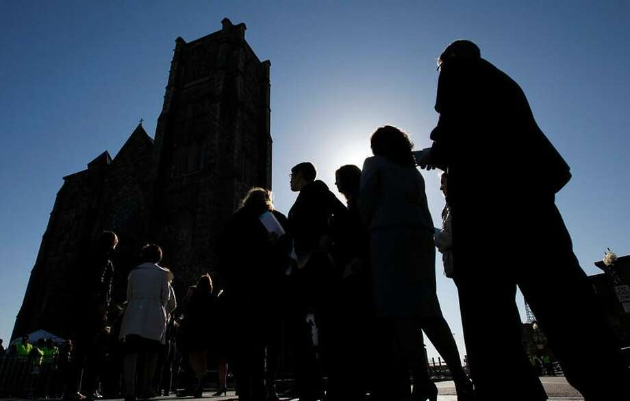 People queue for security check outside the Cathedral of the Holy Cross where U.S. President Barack Obama is scheduled to attend an interfaith service for the victims of the Boston Marathon bombings in Boston, Massachusetts April 18, 2013. Obama was due to visit Boston on Thursday to attend a memorial service for victims of the Boston Marathon bombing amid a manhunt for a suspect seen on video taken before two blasts struck near the finish line on Monday.  REUTERS/Jessica Rinaldi Photo: Reuters / X01704