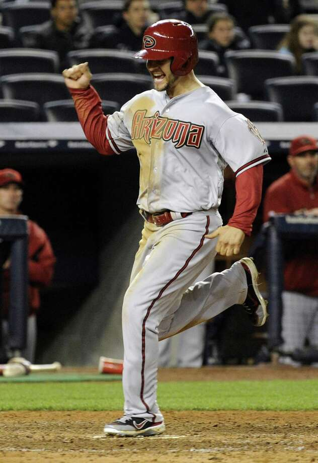 Arizona Diamondbacks' Cody Ross celebrates as he scores on a three-RBI double by Eric Chavez during the 12th inning of a baseball game against the New York Yankees, Thursday, April 18, 2013, at Yankee Stadium in New York. The Diamondbacks won 6-2. (AP Photo/Bill Kostroun) Photo: ASSOCIATED PRESS / AP2013
