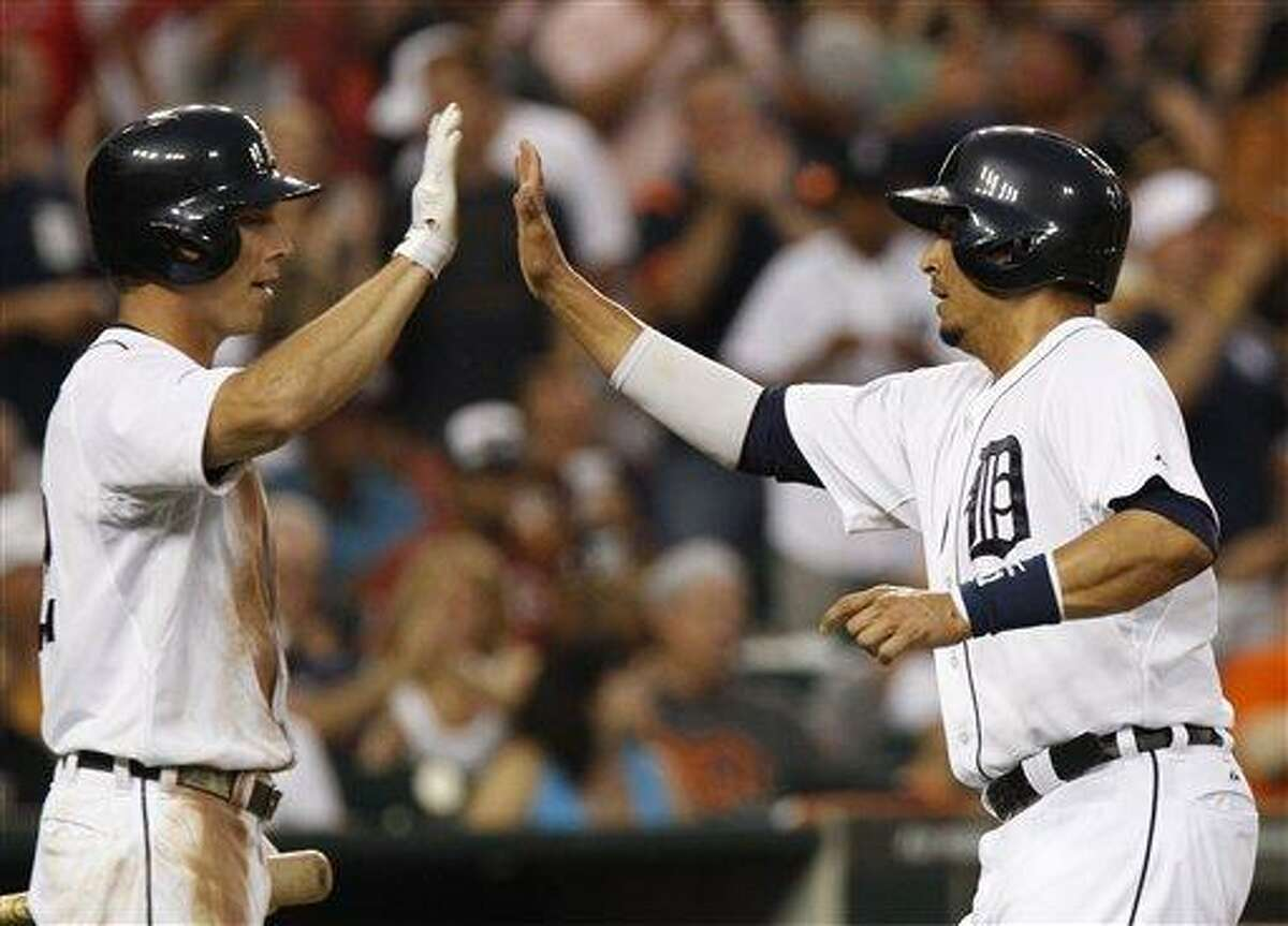 Detroit Tigers' Victor Martinez, right, gets a high-five from Andy Dirks after scoring from second base on a single by Jhonny Peralta in the fifth inning of a baseball game Saturday, June 22, 2013, in Detroit. (AP Photo/Duane Burleson)