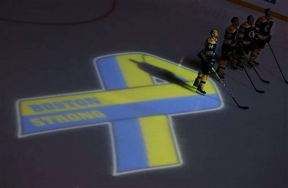 Boston Bruins starters, including defenseman Dennis Seidenberg (44), stand next to a ribbon projected onto the ice at TD Garden in Boston, Wednesday, April 17, 2013, during a ceremony before an NHL hockey game against the Buffalo Sabres in the aftermath of Monday's Boston Marathon bombings. (AP Photo/Elise Amendola) Photo: AP / AP