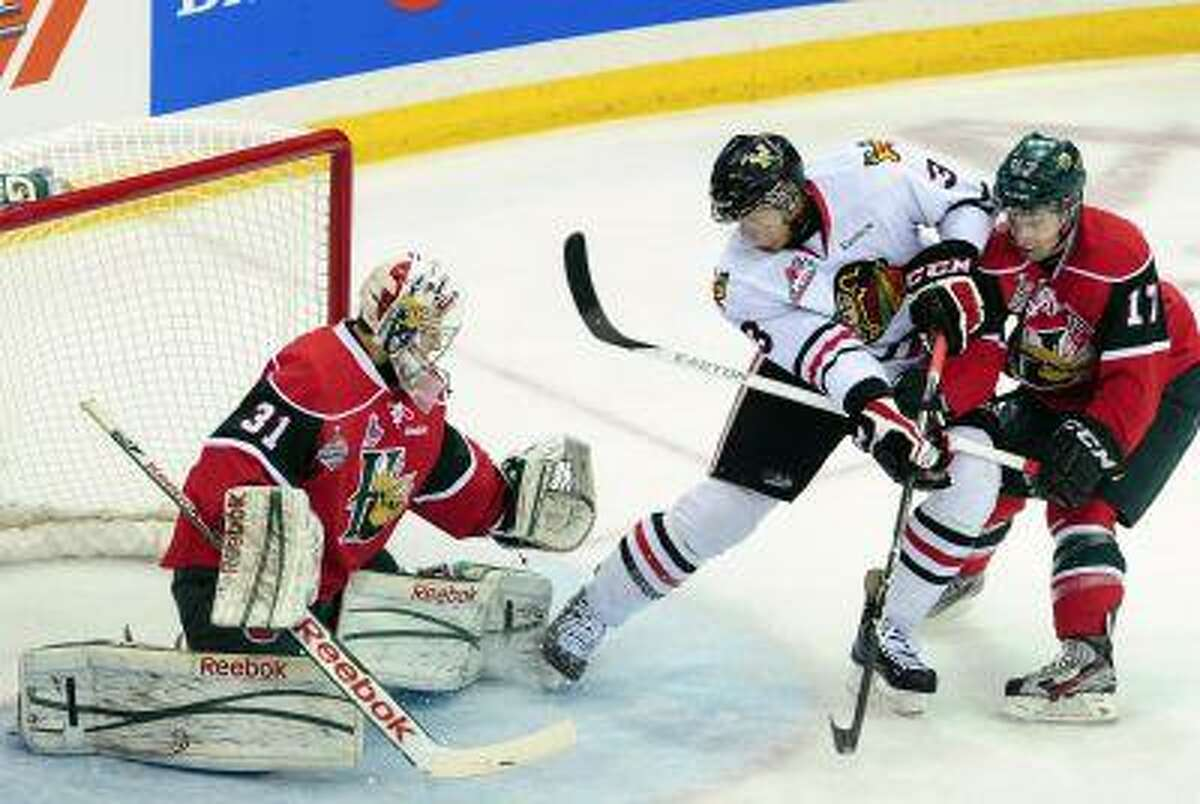 In this May 26, 2013, file photo, Portland Winterhawks defenseman Seth Jones, center, goes to the net in front of Halifax Mooseheads right winger Darcy Ashley, right, as Mooseheads goaltender Zachary Fucale defens during the first period of the Memorial Cup final hockey game in Saskatoon, Saskatchewan. Jones, the son of former NBA basketball player Ronald