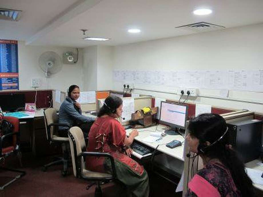 Anita Daniel, left, and other women answer phones at a new hotline in New Dehli on June 14 designed to help women.