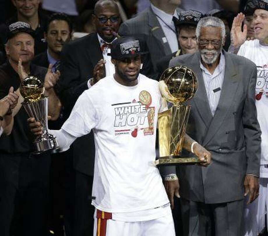 Miami Heat's LeBron James holds the Bill Russell NBA Finals Most Valuable Player Award in his left hand and the Larry O'Brien NBA Championship Trophy after Game 7 of the NBA basketball championships, Friday, June 21, 2013, in Miami. The Miami Heat defeated the San Antonio Spurs 95-88 to win their second straight NBA championship. Bill Russell is at rear. Photo: AP / AP