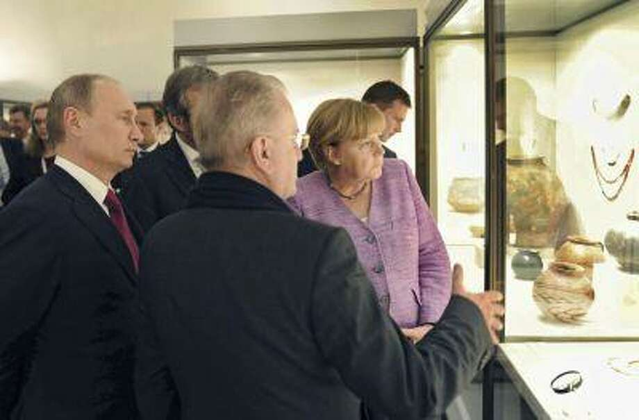 """Russia's President Vladimir Putin and Germany's Chancellor Angela Merkel listen to Director of the State Hermitage Museum Mikhail Piotrovsky as they visit the exhibition """"The Bronze Age of Europe: Europe Without Borders"""" at the State Hermitage Museum in St. Petersburg, June 21, 2013. Photo: REUTERS / X02356"""