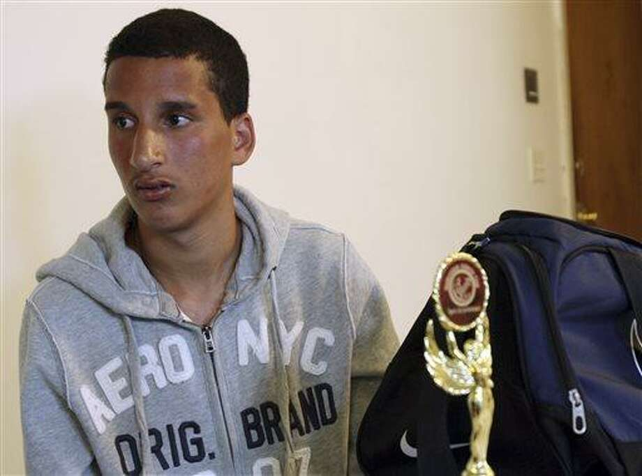 Salah Eddin Barhoum sits in his apartment in Revere, Mass., Thursday, April 18, 2013, with one of the trophies he won in an athletic competition, and the bag he was carrying on Monday near the finish line of the Boston Marathon. The 17-year-old from Morocco, whose photograph appeared on the front page of the New York Post in connection with the Boston Marathon bombings, told The Associated Press he has been scared to go outside because he worries people will blame him for Monday's attack. (AP Photo/Rodrique Ngowi) Photo: AP / AP