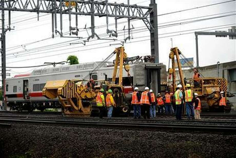 A derailed Metro-North rail car is hoisted back on to the tracks in Bridgeport. Conn. on Sunday, May 19, 2013. Crews will spend days rebuilding 2,000 feet of track, overhead wires and signals following the collision between two trains Friday evening that injured 72 people, Metro-North President Howard Permut said Sunday. (AP Photo/The Connecticut Post,Brian A. Pounds ) MANDATORY CREDIT Photo: AP / The Connecticut Post