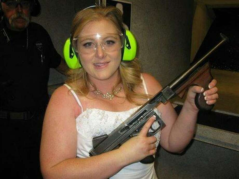 """This July 28, 2012 photo provided by Bob MacDuff shows Lindsae MacDuff holding an automatic weapon at the Gun store in Las Vegas after her """"shotgun wedding."""" One Las Vegas shooting range is selling """"take a shot at love"""" packages that include 50 submachine gun rounds. Another is offering wedding packages in which the bride and groom can pose with Uzis and ammunition belts. And a third invites lovebirds to renew their vows and shoot a paper cutout zombie in the face. (AP Photo/Bob MacDuff) Photo: AP / Bob MacDuff"""