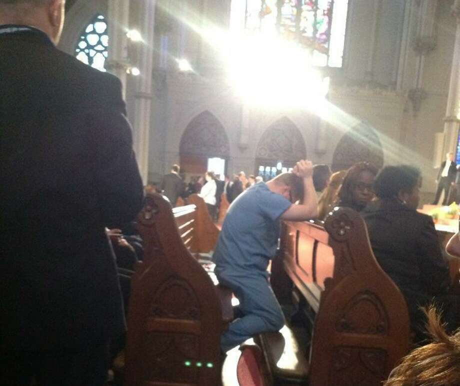 A man in hospital scrubs kneels in a pew at the Cathedral of the Holy Cross in Boston before the interfaith vigil. Sarah Favot/Lowell Sun