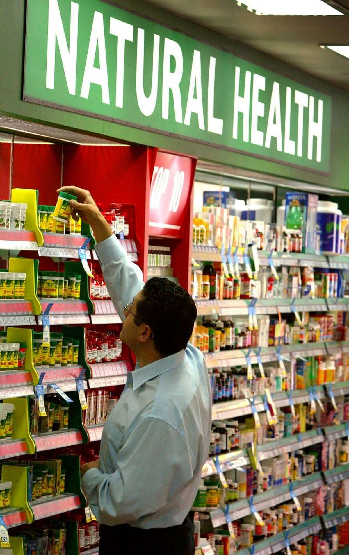 Store worker Sam Issa checks the brand names of rows of herbal, vitamin and mineral pill products at a suburban pharmacy in Sydney April 29, 2003. Australians were urged not to panic over the biggest medical recall in the nation's history which could spread to thousands of over-the-counter drugs and exports of non-prescription medicines in Asia and Europe. Pan Pharmaceuticals, Australia's largest maker of herbal, vitamin and mineral pills (better known as 'complimentary medicines'), is accused of potentially harmful safety and quality breaches in making its own products and goods for other brands. The government's Therapeutic Goods Administration (TGA) has warned Australians to delay taking vitamin and herbal supplements, and the Pharmecy Guild of Australia said confusion reigned as to which products they had to advise their members to remove from their shelves until they new which ones contained Pan ingredients. REUTERS/David Gray