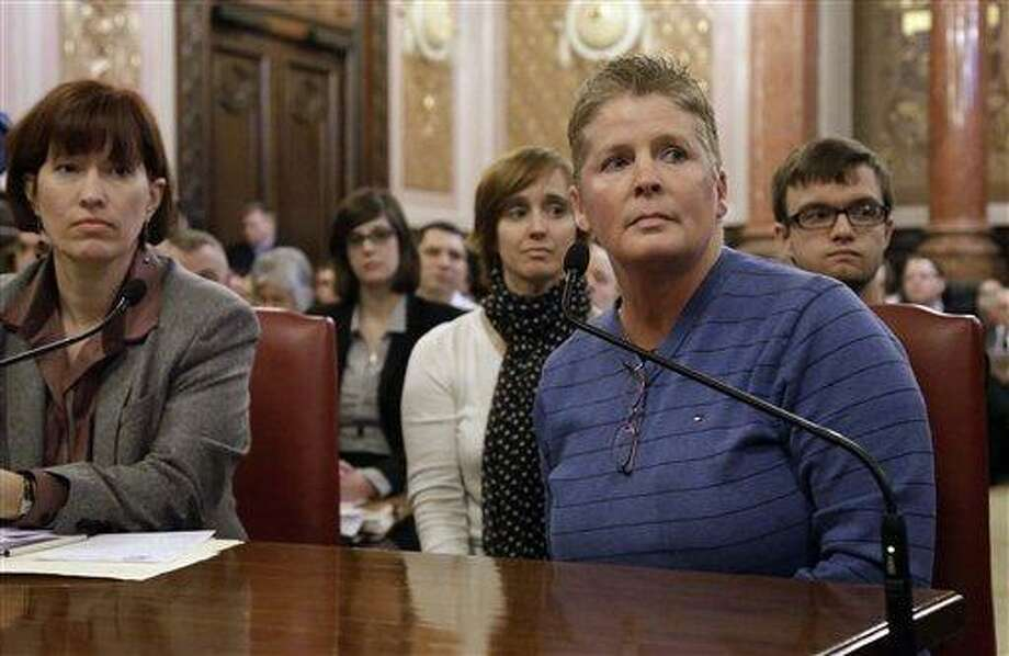 FILE - In this Feb. 5, 2013 file photo, Illinois Sen. Heather Steans, D-Chicago, far left, Bloomington, Ill., resident Danielle Cook, front center, who is in a civil union with her partner of many years, Suzie Hutton, back left, and their 15-year-old son Caleb, right, listen to lawmakers while testifying during a Senate Executive Committee hearing at the Illinois State Capitol in Springfield, Ill. The Illinois Senate is expected to vote on the bill to end Illinois' ban on same-sex marriage Thursday, Feb. 14, 2013.  (AP Photo/Seth Perlman, File) Photo: AP / AP