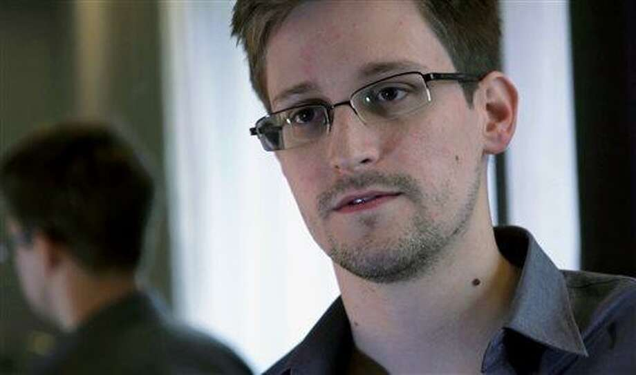 FILE - This June 9, 2013 photo provided by The Guardian newspaper in London shows Edward Snowden, who worked as a contract employee at the U.S. National Security Agency, in Hong Kong. The Guardian newspaper says that the British eavesdropping agency GCHQ repeatedly hacked into foreign diplomats' phones and emails when the U.K. hosted international conferences, even going so far as to set up a bugged Internet café in an effort to get an edge in high-stakes negotiations. The Guardian cites more than half a dozen internal government documents provided by former NSA contractor Edward Snowden as the basis for its reporting on GCHQ's intelligence operations. (AP Photo/The Guardian, File) Photo: AP / TGRDN