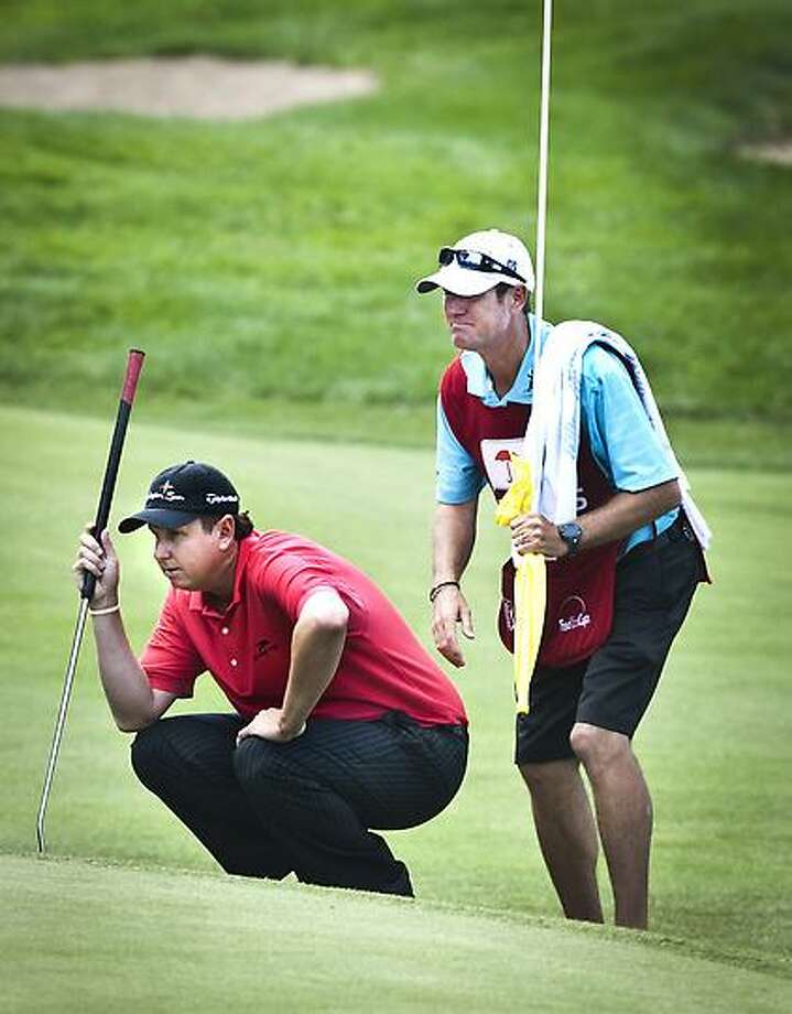 Melanie Stengel -- Register J..J. Henry and his caddy line up a putt on the 17th hole 6/21.