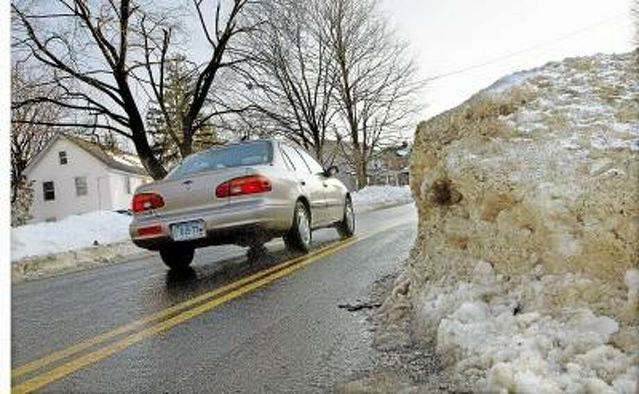 Catherine Avalone/The Middletown Press Motorists were forced to drive in the opposite lane around a mound of snow at the corner of Highland Avenue and Bretton Road in Middletown until late Thursday afternoon.